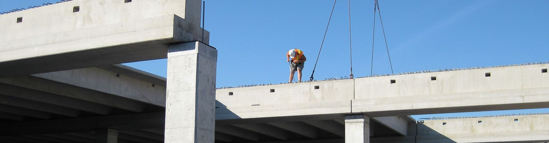 worker standing on cross beam being positioned